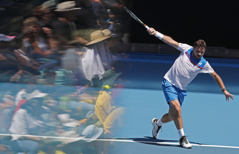 Switzerland's Stan Wawrinka makes a backhand return to Damir Dzumhur of Bosnia and Herzegovina during their first round singles match at the Australian Open tennis championship in Melbourne, Australia, Tuesday, Jan. 21, 2020. (AP Photo/Andy Wong)