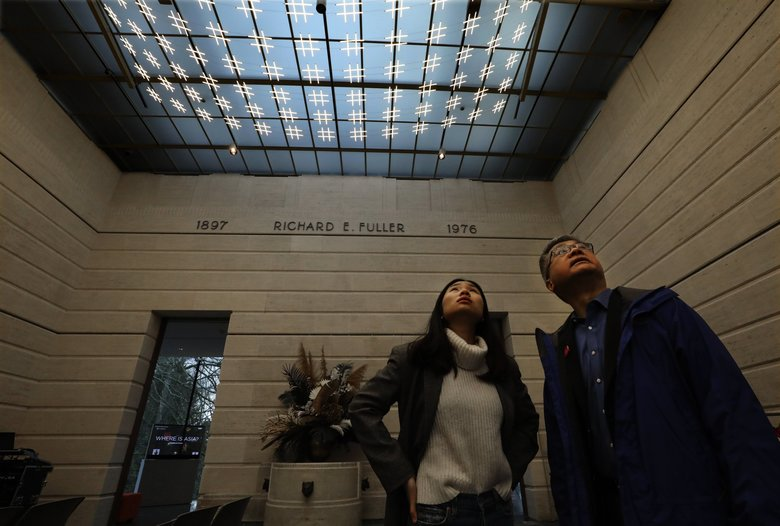 Former Gov. Gary Locke and his daughter Emily check out the light sculpture in the Garden Court of the Seattle Asian Art Museum. (Alan Berner / The Seattle Times)
