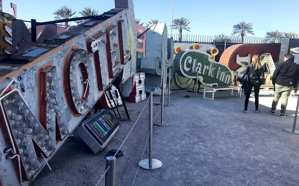 Visitors walk through the Neon Boneyard at Las Vegas' Neon Museum, where over 200 neon signs are displayed around a central path. The Neon Museum collects and preserves and restores Las Vegas' historic neon signs. (Megan Burbank / The Seattle Times)