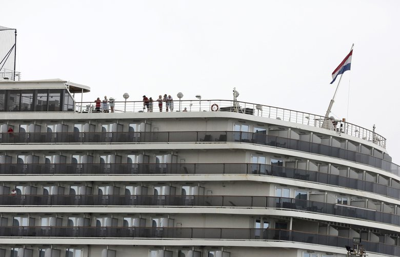 Passengers stand on the top deck of the MS Westerdam while the cruise ship is docked in Sihanoukville, Cambodia Monday, Feb. 17, 2020. The feel-good story of how Cambodia allowed a cruise ship to dock after it was turned away elsewhere in Asia for fear of spreading the deadly virus that began in China has taken a dark turn after a passenger released from the ship tested positive for the virus. (AP Photo) TKMY402 TKMY402