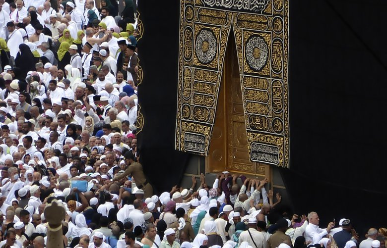 In this Feb. 24, 2020, photo, Muslim pilgrims pray near the Kaaba, the cubic building at the Grand Mosque, as worshippers circumambulate around during the minor pilgrimage, known as Umrah in the Muslim holy city of Mecca, Saudi Arabia. Saudi Arabia halted Thursday, Feb. 27 travel to the holiest sites in Islam over fears of the global outbreak of the new coronavirus just months ahead of the annual hajj pilgrimage, a move coming as the Mideast has over 220 confirmed cases of the illness. (AP Photo/Amr Nabil) AMR102 AMR102