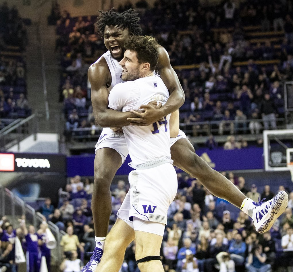 Washington Huskies forward Isaiah Stewart (33) excitedly jumps into the arms of Huskies forward Sam Timmins (14) after Timmins did a behind the back pass to Huskies guard Jamal Bey (5) for a basket in a game against Stanford Cardinal on Thursday, Feb. 20, 2020 at Alaska Airlines Arena. (Amanda Snyder / The Seattle Times)