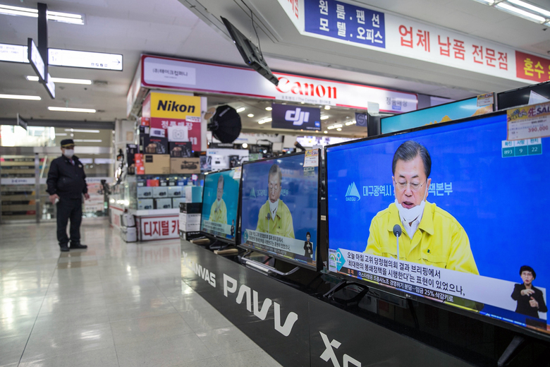 """A television at an electronics store shows television news coverage of a speech by President Moon Jae-in of South Korea in Seoul on Tuesday, Feb. 25. Two weeks ago, Moon predicted that the coronavirus outbreak would """"disappear before long."""" (Jean Chung/The New York Times)"""