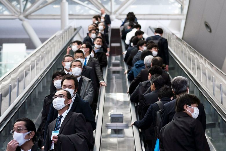 People wearing face masks ride escalators on Thursday in Tokyo, Japan. (Tomohiro Ohsumi/Getty Images AsiaPac)