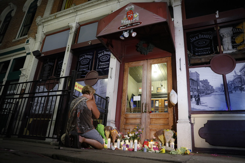 FILE—In this file photo from Aug. 4, 2019, mourners visit a makeshift memorial outside Ned Peppers bar following a vigil at the scene of the mass shooting in Dayton, Ohio. Trey Landers, a Dayton native and senior guard on the University of Dayton basketball team was there when a masked gunman in body armor opened fire early that Sunday. He has now helped his basketball team to its best start ever at 26-2 and to No. 4 in the current Associated Press poll, its highest ranking in 64 years.   (AP Photo/John Minchillo, File)