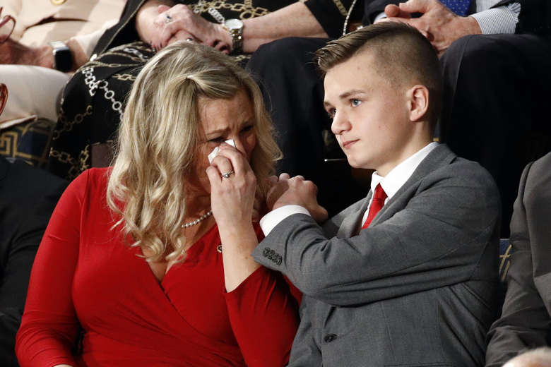 Kelli and Gage Hake of Stillwater, Okla., cry as they are recognized by President Donald Trump during his State of the Union address to a joint session of Congress on Capitol Hill in Washington, Tuesday, Feb. 4, 2020. She is the widow of Army Staff Sgt. Christopher Hake, who was killed while serving his second tour of duty in Iraq. (AP Photo/Patrick Semansky)