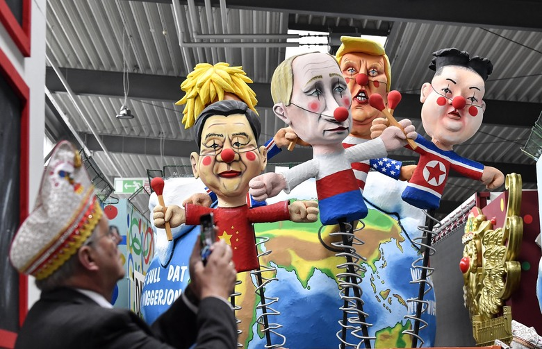 A satiric carnival float depicting the leaders of China, United Kingdom, Russia, USA and North Korea, Xi Jinping, Boris Johnson, Vladimir Putin, Donald Trump and Kim Jong-un as puppets is watched by a reveller during a preview in a hall in Cologne, Germany, Tuesday, Feb. 18, 2020. The traditional carnival parades on Rosemonday make fun of politics and are watched by hundreds of thousands in the streets of Cologne, Duesseldorf and Mainz. (AP Photo/Martin Meissner)