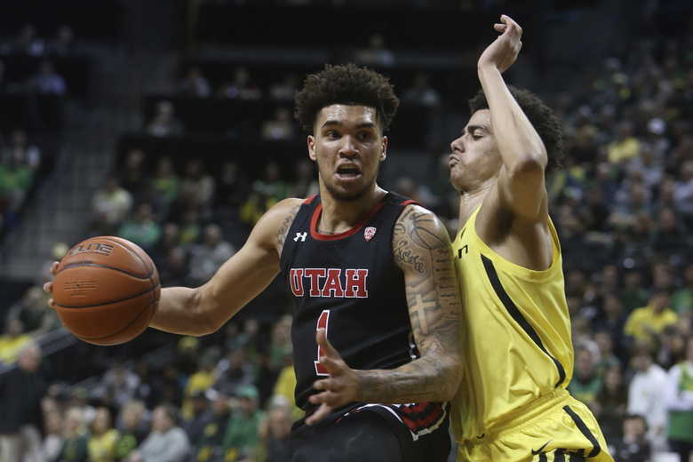 Utah's Timmy Allen, left, maneuvers against Oregon's Will Richardson during the second half of an NCAA college basketball game in Eugene, Ore., Sunday, Feb. 16, 2020. (AP Photo/Chris Pietsch)