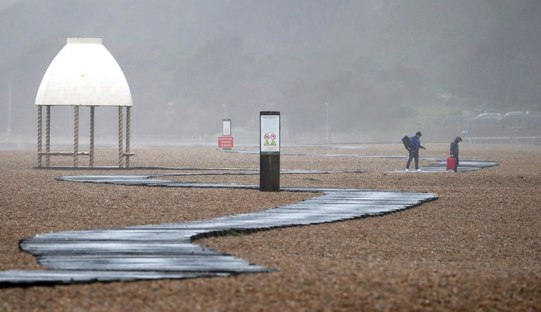 """People walk along the beach in Folkestone, as the effects of Storm Dennis continue to cause problems across the country, in Kent, England, Sunday, Feb. 16, 2020. Storm Dennis roared across Britain on Sunday, lashing towns and cities with high winds and dumping so much rain that authorities urged residents to protect themselves from """"life-threatening floods"""" in Wales and Scotland.  (Gareth Fuller/PA via AP)"""