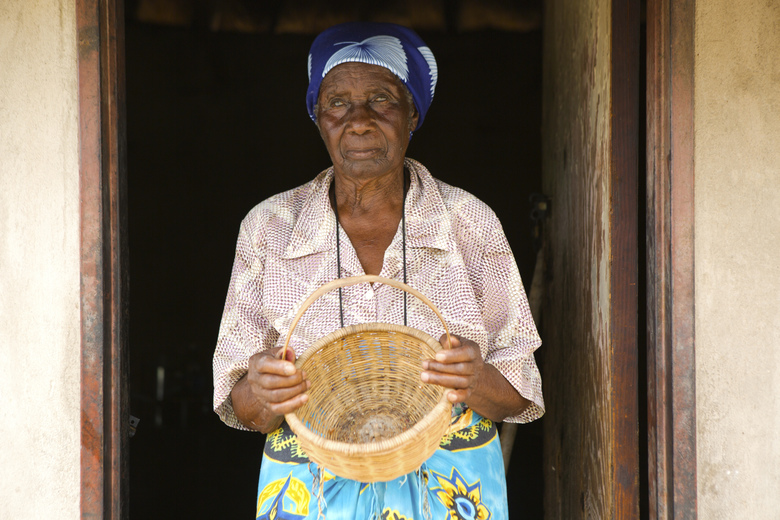 In this Thursday, Feb. 20, 2020, Leah Tsiga, stands outside her thatched hut with an empty basket in Mudzi about 230 Kilometers, northeast of the Zimbabwean capital Harare. Living alone in Zimbabwe's arid Mudzi district, Leah Tsiga's best friend is her cat. But when it comes to food, each has to look for their own and the 90-year-old Tsiga often comes second best. The crafty feline forages in nearby bushes for rats, birds, insects and worms. As for the frail Tsiga, she sometimes goes for days without a solid meal, as Zimbabwe is ravaged by a combination of drought and deepening economic crisis. (AP Photo/Tsvangirayi Mukwazhi)