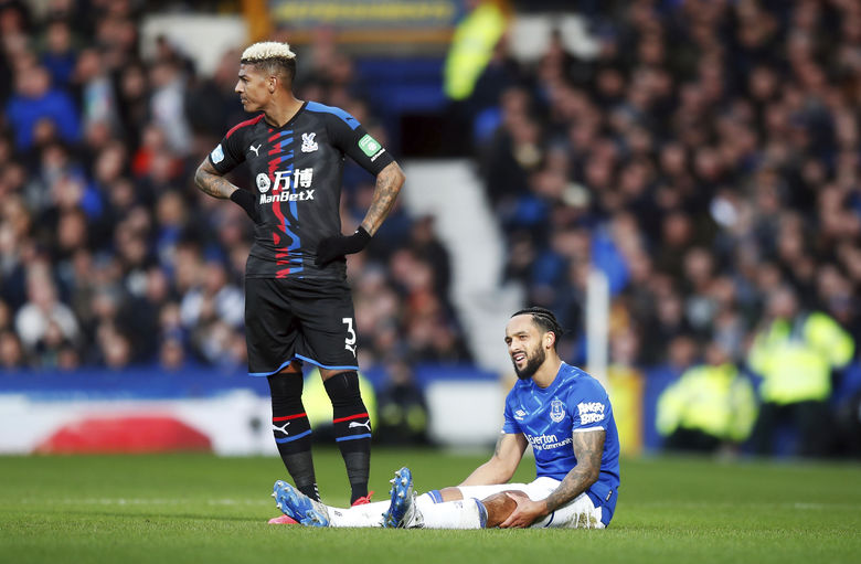Everton's Theo Walcott sits on the pitch before being substituted with an injury during the English Premier League soccer match between Everton and Crystal Palace at Goodison Park, in Liverpool, England,  Saturday, Feb. 8, 2020. (Martin Rickett/PA via AP)