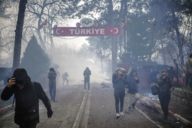 Greek border guards use teargas to push back migrants who try to enter Greece at the Pazarkule border gate, Edirne, Turkey, Saturday, Feb. 29, 2020. (Ismail Coskun/IHA via AP)