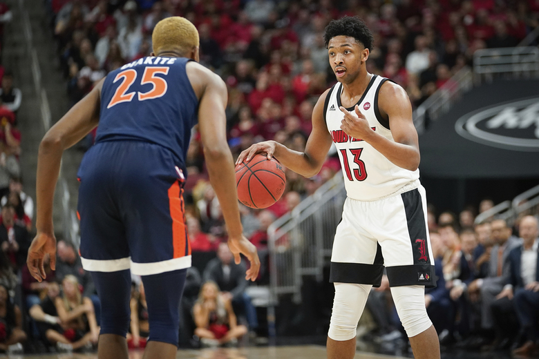 Louisville guard David Johnson (13) signals to a teammate during the second half of an NCAA college basketball game against Virginia, Saturday, Feb 8, 2020 in Louisville, Ky. (AP Photo/Bryan Woolston)