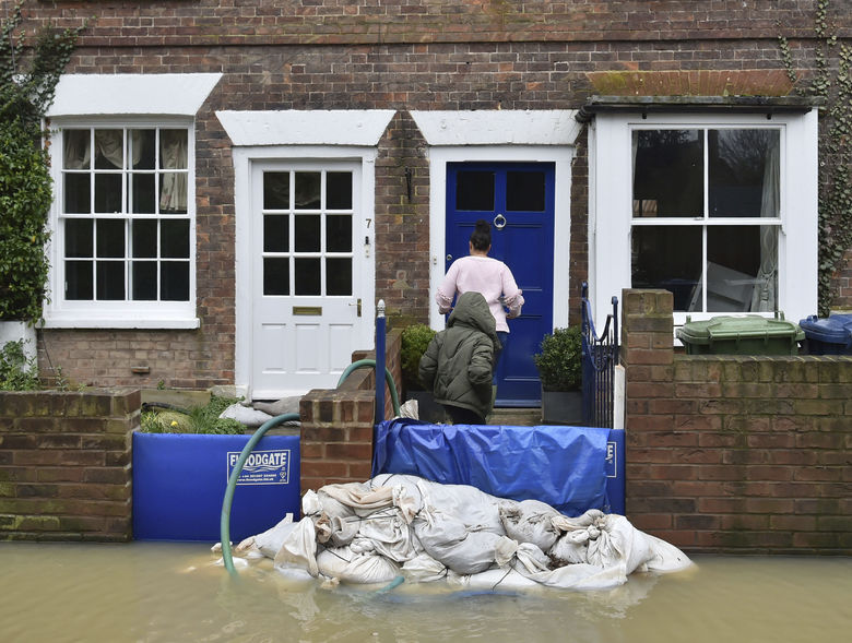 People enter a cottage as pumps and flood barriers help to keep the water from flooding the homes, with the area inundated by flood water after heavy rains breached normal watercourses in Tewkesbury, England, Wednesday Feb. 19, 2020. Flood-hit communities in the region are braced for further heavy rain as river levels continue to threaten to breach barriers, in the aftermath of Storm Dennis which has swept northern Europe. (Ben Birchall/PA via AP)