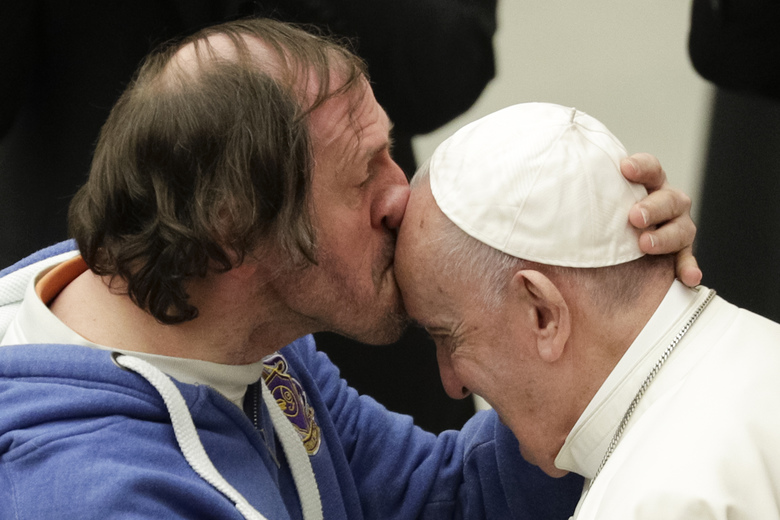 Pope Francis is kissed by a man during his weekly general audience, at the Pope Paul VI hall, at the Vatican, Wednesday, Feb. 19, 2020. (AP Photo/Andrew Medichini)