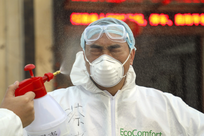In this Monday, Feb. 3, 2020, photo, a worker in a protective suit is disinfected outside a hotel being used for people held in medical isolation in Wuhan in central China's Hubei province. Hong Kong hospitals cut services as medical workers were striking for a second day Tuesday to demand the border with mainland China be shut completely to ward off a virus that caused its first death in the semi-autonomous territory. (Chinatopix via AP)