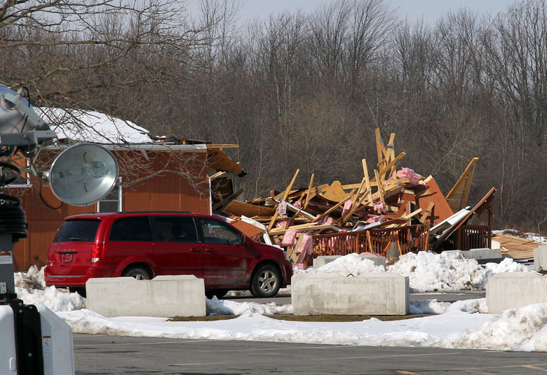 In this Feb. 22, 2020 photo, a vehicle is parked near a partially demolished building on the Cayuga Indian Nation in Seneca Falls, N.Y. A leadership dispute within the Cayuga Indian Nation took a stunning turn over the weekend when nation leader Clint Halftown sent bulldozers to demolish a working daycare center, store, schoolhouse and other buildings controlled by tribe members who oppose his authority, drawing condemnation from local and federal officials who called the action domestic terrorism. Halftown has not responded to requests for an interview. (Spencer Tulis/Finger Lakes Times via AP)