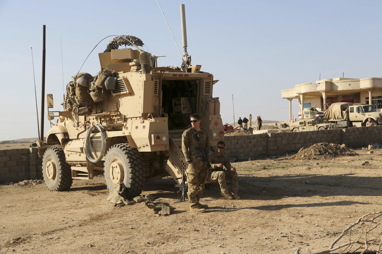 FILE – In this Feb. 23, 2017 file photo, U.S. Army soldiers stand outside their armored vehicle on a joint base with the Iraqi army, south of Mosul, Iraq. As Iraqi forces push into western Mosul coalition troops are closer to frontline fighting than ever before. The Iraqi government has told its military not to seek assistance from the U.S.-led coalition forces in operations against the Islamic State group, two senior Iraqi military officials said. The move comes amid a crisis of mistrust tainting U.S.-Iraq ties after an American strike killed Soleimani and an Iraqi militia commander. (AP Photo/ Khalid Mohammed, File)