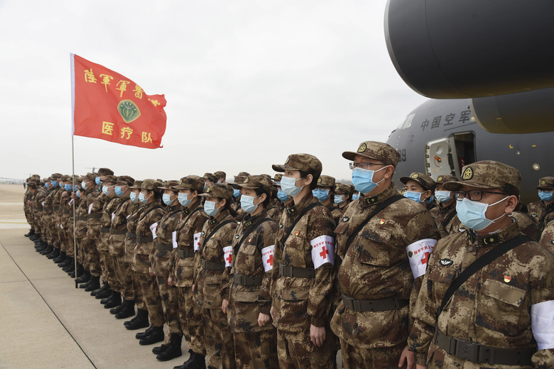 In this photo released by China's Xinhua News Agency, Chinese military medics arrive at the Tianhe International Airport in Wuhan, central China's Hubei Province, Feb. 13, 2020. China has mobilized its military resources in its fight against the COVID-19 viral outbreak. (Li Yun/Xinhua via AP)
