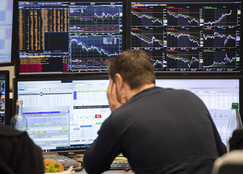 A broker watches his screens with the German stock index DAX in background at the stock market in Frankfurt, Germany, Friday, Feb. 28, 2020. (Boris Roessler/dpa via AP)
