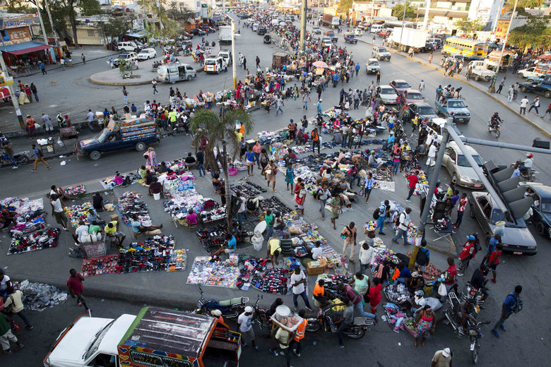 In this Feb. 11, 2020 photo, street vendors work in Port-au-Prince, Haiti. Two years after the departure of U.N. peacekeepers, young bandits randomly halt cars,  the economy appears to be shrinking and electricity comes only a few hours a day. (AP Photo/Dieu Nalio Chery)