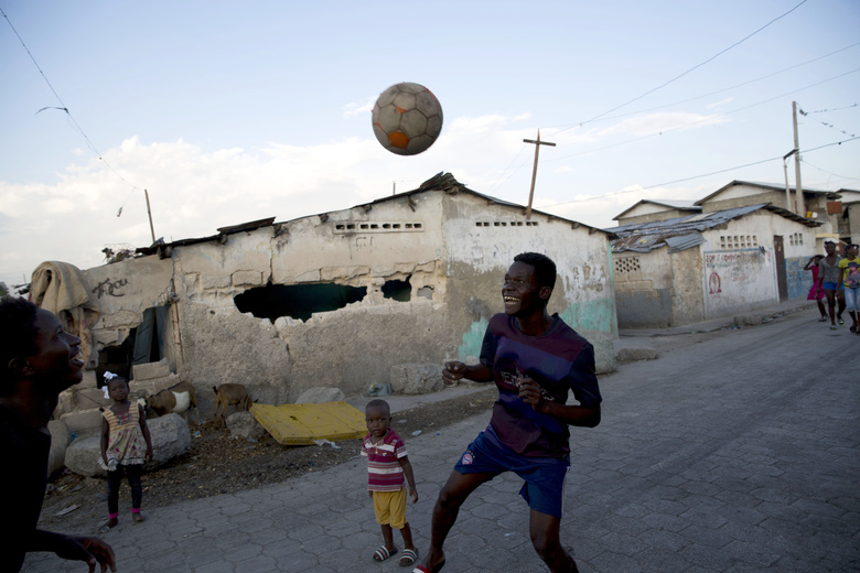 In this Feb. 11, 2020 photo, youths play soccer in the Cite Soleil slum of Port-au-Prince, Haiti. Haiti's economy appears to be shrinking and electricity comes only a few hours a day in most of the capital. (AP Photo/Dieu Nalio Chery)