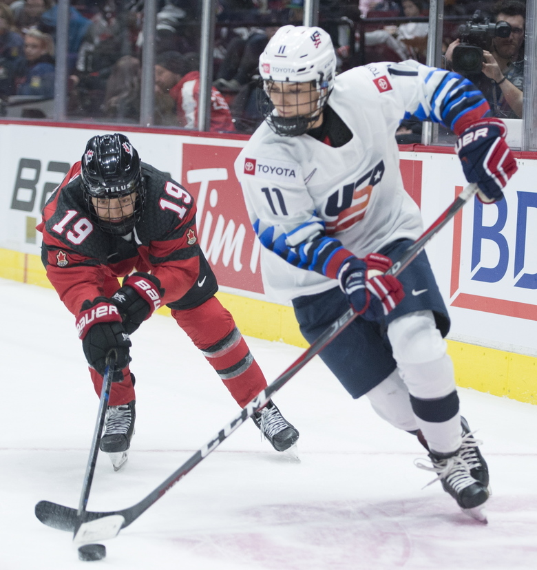 Canada's Brianne Jenner fights for control of the puck with United States' Sophia Shaver during the second period of a Rivalry Series hockey game in Vancouver, British Columbia, Wednesday, Feb. 5, 2020. (Jonathan Hayward/The Canadian Press via AP)