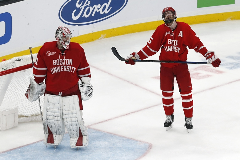 Boston University's Cam Crotty (5) stands with goalie Sam Tucker after the goal by Northeastern's Jordan Harris in double overtime during the Beanpot Tournament championship NCAA college hockey game in Boston, Monday, Feb. 10, 2020. (AP Photo/Michael Dwyer)
