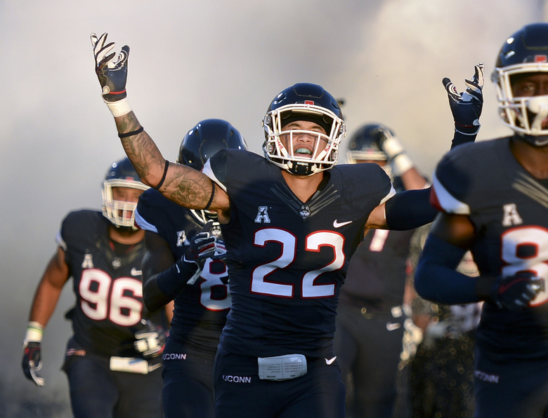 FILE – In this Aug. 30, 2018, file photo, Connecticut linebacker Eli Thomas (22) raises his arms to the crowd as his team enters the field for their season-opening NCAA college football game against Central Florida in East Hartford, Conn. Thomas, who overcame a stroke to return to school, is among the first six athletes named as finalists for the Hartford HealthCare Courage Award. (AP Photo/Stephen Dunn, File)