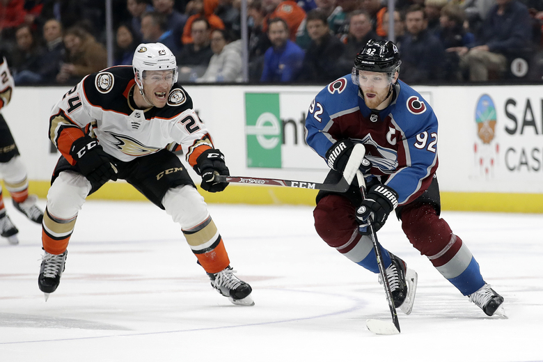 Colorado Avalanche's Gabriel Landeskog, right, is defended by Anaheim Ducks' Carter Rowney (24) during the first period of an NHL hockey game Friday, Feb. 21, 2020, in Anaheim, Calif. (AP Photo/Marcio Jose Sanchez)