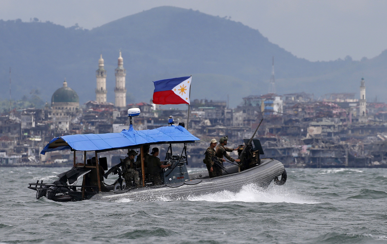 "FILE – In this Oct. 19, 2017, file photo, Philippine Navy commandos aboard a gunboat patrol the periphery of Lake Lanao as smoke rises from the ""Main Battle Area"" where pro-Islamic group militants made a final stand amid a massive military offensive of Marawi city in southern Philippines. President Donald Trump contended this week that the United States saved the Philippines from Islamic State terrorism. His assertion vastly overstated both the threat IS posed to the country and what the U.S. did about it. (AP Photo/Bullit Marquez, File)"