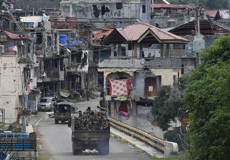 FILE – In this Oct. 19, 2017, file photo, Philippine troops head back to the devastated village of Mapandi which has been cleared of Islamic State group-linked militants in Marawi city in southern Philippines. President Donald Trump contended this week that the United States saved the Philippines from Islamic State terrorism. His assertion overstated both the threat IS posed to the country and what the U.S. did about it.. (AP Photo/Bullit Marquez, File)