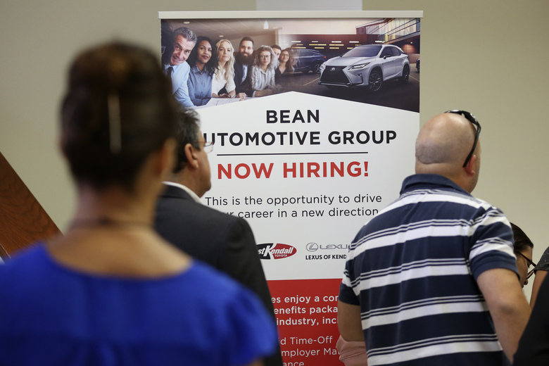 FILE – In this Sept. 18, 2019, file photo people stand in line to inquire about jobs available at the Bean Automotive Group during a job fair designed for people fifty years or older in Miami. On Tuesday, Feb. 11, 2020, the Labor Department reports on job openings and labor turnover for December. (AP Photo/Lynne Sladky, File)
