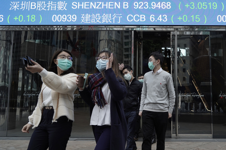 People wearing protective face masks, walk on a street in the Central, the business district of Hong Kong, Tuesday, Feb. 11, 2020. China's daily death toll from new virus has topped 100 for first time, with more than 1,000 total deaths recorded, the health ministry announced Tuesday, as the spread of the contagion shows little sign of abating while exacting an ever-rising cost. (AP Photo/Kin Cheung)