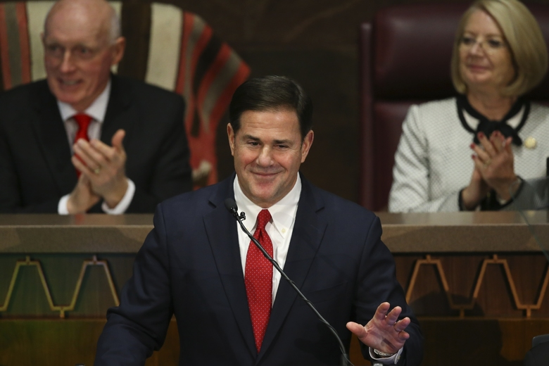 """FILE – In this Jan. 13, 2020 file photo Arizona Republican Gov. Doug Ducey, foreground, gestures during his State of the State address as Senate president Karen Fann, R-Prescott, right, and House Speaker Rusty Bowers, R-Mesa, left, listen in on the opening day of the legislative session at the Capitol in Phoenix. Ducey and Republican lawmakers have pulled a contentious proposal to enshrine a ban on so-called """"sanctuary cities"""" in the state constitution. The decision announced late Thursday, Feb. 20, 2020, comes on the eve of a House hearing on the proposal the Republican governor asked lawmakers to send to voters. (AP Photo/Ross D. Franklin,File)"""