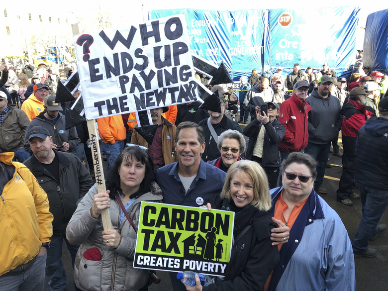 Knute Buehler, a Republican candidate for Congress, poses with demonstrators who oppose a climate-change bill written by majority Democrats in the statehouse, at the Oregon State Capitol in Salem. (Andrew Selsky / The Associated Press)
