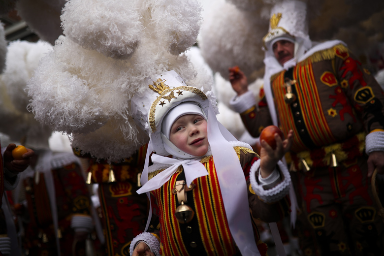 A young 'Gilles of Binche' throws an orange during a traditional carnival parade in Binche, Belgium, Tuesday, Feb. 2020.  During the parade, clown-like performers known as Gilles throw oranges to the crow, which are considered carrying good luck. (AP Photo/Francisco Seco)