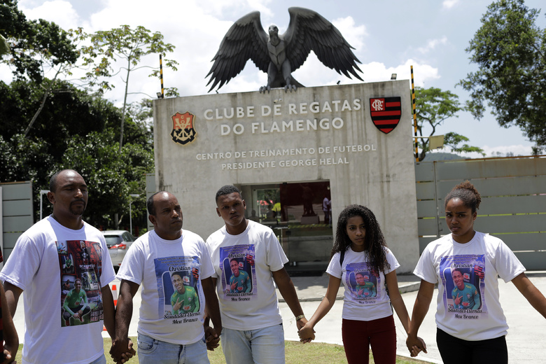 """Relatives of the young soccer players who died one year ago in a fire at the Flamengo club training center, pray outside the training center in Rio de Janeiro, Brazil, Saturday, Feb. 8, 2020. Saturday marked one year since the fire killed 10 of Flamengo's academy players, all between 14 and 16 years old. It was """"the worst tragedy"""" in the team's 124-year history, club president Rodolfo Landim has repeatedly said since. (AP Photo/Silvia Izquierdo)"""