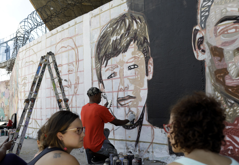 A mural featuring the faces of young soccer players who died one year ago in a fire at the Flamengo club training center is painted in front of Maracana stadium in Rio de Janeiro, Brazil, Friday, Feb. 7, 2020. The fire killed 10 academy players and injured three others, all aged between 14 and 16 years-old at the time. (AP Photo/Silvia Izquierdo)