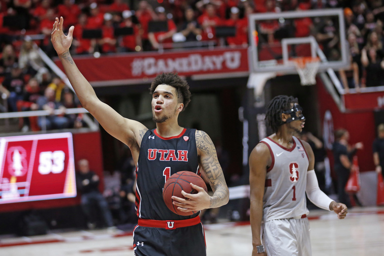 Utah forward Timmy Allen (1) celebrates as Stanford guard Daejon Davis (1) looks away in overtime of an NCAA college basketball game Thursday, Feb. 6, 2020, in Salt Lake City. Utah won 64-56. (AP Photo/Rick Bowmer)