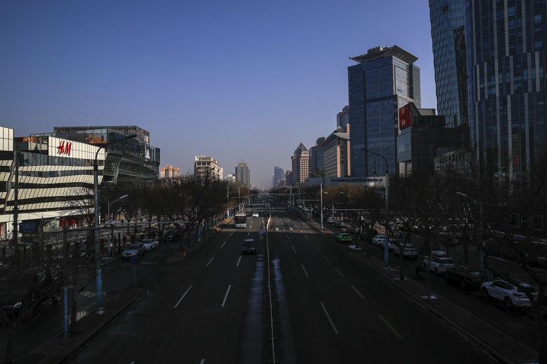 Vehicles move down a quiet road near the capital city's popular shopping malls in Beijing, Monday, Feb. 10, 2020. China reported a rise in new virus cases on Monday, possibly denting optimism that its disease control measures like isolating major cities might be working, while Japan reported dozens of new cases aboard a quarantined cruise ship. (AP Photo/Andy Wong)