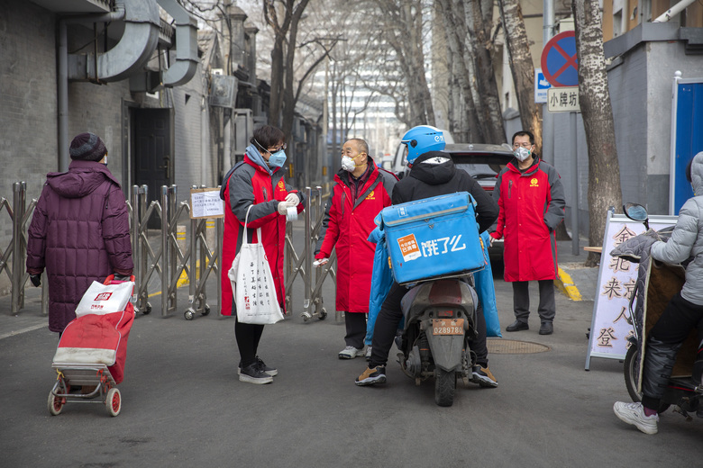 Volunteers in red jackets stand at a barricade at the entrance to a neighborhood in Beijing, Friday, Feb. 21, 2020. China reported a further fall in new virus cases to 889 on Friday as health officials expressed optimism over containment of the outbreak that has caused more than 2,200 deaths and is spreading elsewhere. (AP Photo/Mark Schiefelbein)