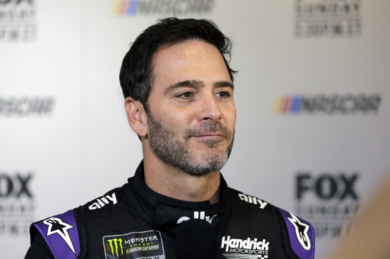 """FILE – In this Feb. 13, 2019, file photo, driver Jimmie Johnson smiles during media day for the NASCAR Daytona 500 auto race at Daytona International Speedway in Daytona Beach, Fla.  As he prepares for his final season of full-time racing, the most accomplished driver of his generation has changed his mindset. """"I'm not chasing anything,"""" said Johnson, who is determined to enjoy his 19th and final Cup season. (AP Photo/Terry Renna, File)"""