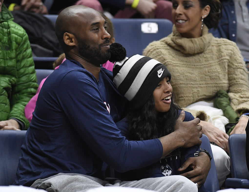 FILE – In this March 2, 2019, file photo Kobe Bryant and his daughter Gianna watch the first half of an NCAA college basketball game between Connecticut and Houston in Storrs, Conn. A public memorial service for Bryant, Gianna and seven others killed in a helicopter crash is planned for Monday, Feb. 24, 2020, at Staples Center in Los Angeles, a person with knowledge of the details told The Associated Press on Thursday, Feb. 6, 2020. (AP Photo/Jessica Hill, File)