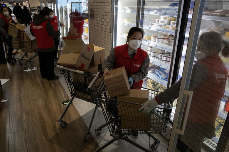 In this Tuesday, Feb. 18, 2020, photo,  workers at the 7Fresh supermarket restock the fridge in Beijing. Stores that offer online purchases are enjoying brisk sales as residents avoid going out during the current viral outbreak with authorities last week requiring people returning to the capital to self-quarantine at home or in a concentrated area for medical observation.(AP Photo/Ng Han Guan)