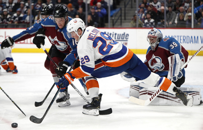 Colorado Avalanche defenseman Nikita Zadorov, left, fights for control of the puck with New York Islanders center Brock Nelson, center, as Colorado goaltender Pavel Francouz protects the net during the second period of an NHL hockey game Wednesday, Feb. 19, 2020, in Denver. (AP Photo/David Zalubowski)