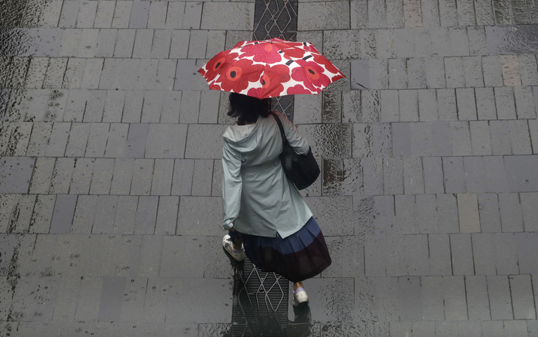 A woman shelters under an umbrella as rain falls in Sydney, Friday, Feb. 7, 2020, while the Bureau of Meteorology issued severe weather warning along the New South Wales state coast. The rain comes as a slight relief for some areas dealing with wildfires that devastated large swathes of land across the state over the last several months. (AP Photo/Rick Rycroft)