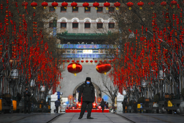 FILE – In this Feb. 16, 2020, file photo, a security guard wearing a face mask walks through a quiet main Qianmen Street, a popular tourist spot in Beijing. As the coronavirus spreads around the world, International health authorities are hoping countries can learn a few lessons from China, namely, that quarantines can be effective and acting fast is crucial. On the other hand, the question before the world is to what extent it can and wants to replicate China's draconian methods. (AP Photo/Andy Wong, File)