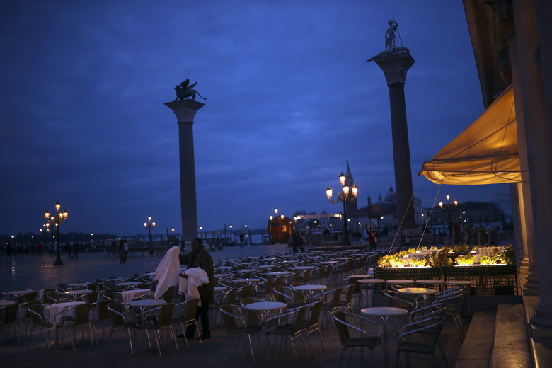 """A worker removes tablecloths in an empty restaurant terrace at the St. Mark's Square in Venice, Saturday, Feb. 29, 2020. A U.S. government advisory urging Americans to reconsider travel to Italy due to the spread of a new virus is the """"final blow"""" to the nation's tourism industry, the head of Italy's hotel federation said Saturday. Venice, which was nearing recovery in the Carnival season following a tourist lull after record flooding in November, saw bookings drop immediately after regional officials canceled the final two days of celebrations this week, unprecedented in modern times. (AP Photo/Francisco Seco)"""