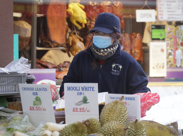 """A woman wears a mask as she works on a food stall in China Town in London, Friday, Feb. 7, 2020. The director-general of the World Health Organization says a drop in the number of new coronavirus cases for two days is """"good news"""" but cautions against reading too much into that. China reported 31,161 cases in mainland China in its update Friday. (AP Photo/Kirsty Wigglesworth)"""